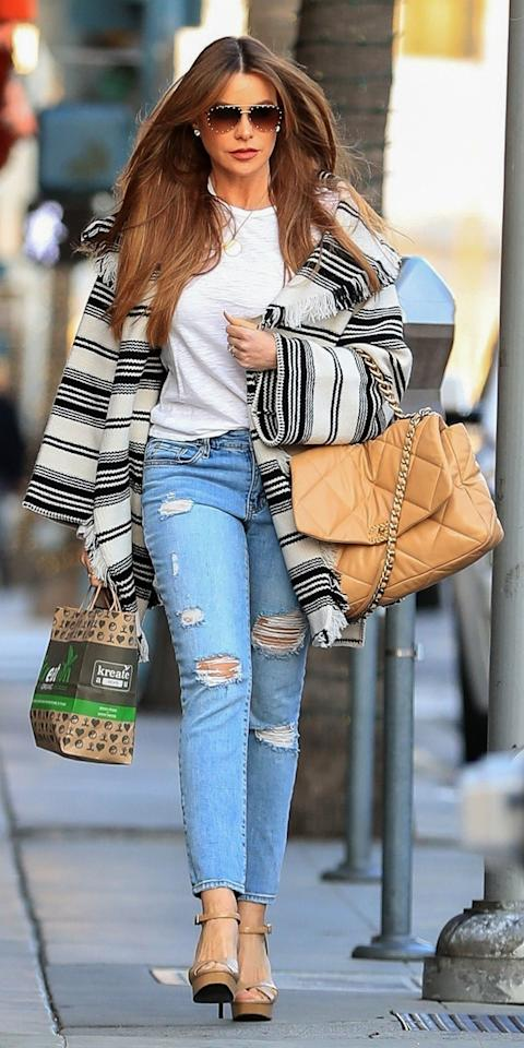 <p>Sofia Vergara was spotted wearing a fringe poncho over a white T-shirt and distressed jeans. She went all out by choosing a jumbo Chanel bag, studded sunglasses, and platform heels as accessories.</p>
