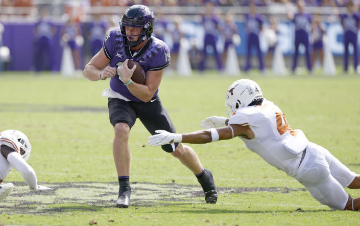 TCU quarterback Max Duggan (15) carries the ball for a first down as Texas defensive back Darion Dunn (4) attempts to make the tackle during the first half of an NCAA college football game Saturday, Oct. 2, 2021, in Fort Worth, Texas. (AP Photo/Ron Jenkins)