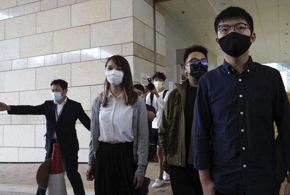 Hong Kong activists, from right, Joshua Wong, Ivan Lam and Agnes Chow arrive at a court in Hong Kong, Monday, Nov. 22. 2020. The trio appears at court for their trial as they face charges related to the besieging of a police station during anti-government protests last year. (AP Photo/Vincent Yu)