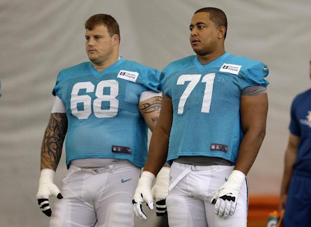 FILE - In this July 24, 2013 file photo, Miami Dolphins guard Richie Incognito (68) and tackle Jonathan Martin (71) stand on the field during an NFL football practice in Davie, Fla. Two people familiar with the situation say suspended Dolphins guard Incognito sent text messages to teammate Jonathan Martin that were racist and threatening. The people spoke to The Associated Press on condition of anonymity because the Dolphins and NFL haven't disclosed the nature of the misconduct that led to Incognito's suspension. Martin remained absent from practice Monday, Nov. 4, 2013, one week after he suddenly left the team. (AP Photo/Lynne Sladky, File)