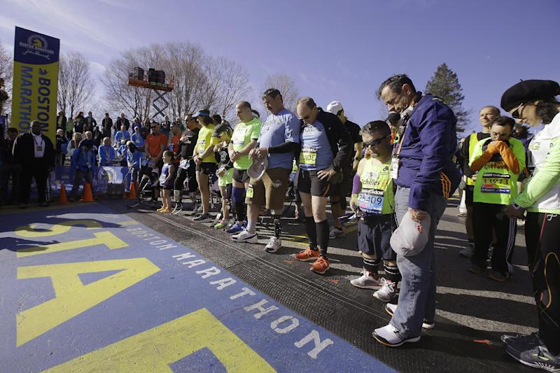 Mobility-impaired runners gather at the start line for a moment of silence before the 118th Boston Marathon Monday, April 21, 2014 in Hopkinton, Mass. (AP Photo/Stephan Savoia)