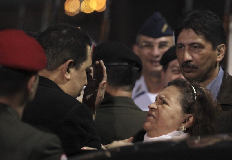 Venezuela's President Hugo Chavez, second left, pauses as his mother, Helena Frias, reaches out to touch his forehead as she says goodbye after their arrival to the Simon Bolivar airport in Maiquetia , Venezuela, Friday March 16, 2012. Chavez, who traveled with his mother from Havana, returned home Friday nearly three weeks after undergoing cancer surgery in Cuba. (AP Photo/Fernando Llano)