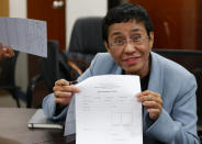 FILE - In this Feb. 13, 2019, file photo,Maria Ressa, the award-winning head of a Philippine online news site Rappler that has aggressively covered President Rodrigo Duterte's policies, shows an arrest form after being arrested by National Bureau of Investigation agents in a libel case in Manila, Philippines. The Nobel Peace Prize was awarded to journalists Ressa of the Philippines and Dmitry Muratov of Russia for their fight for freedom of expression. (AP Photo/Bullit Marquez, File)