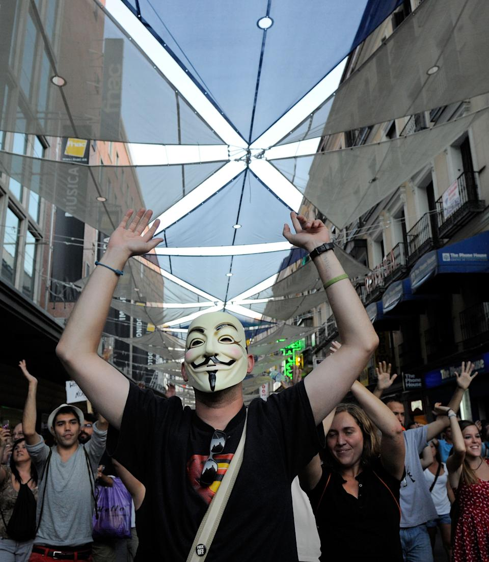 A protester, wearing an anonymous mask, protests after being prevented by police from gathering in Puerta del Sol square on August 2, 2011 in Madrid, Spain. The indignants were protesting high levels of unemployment, the austerity measures and what they consider a stagnant and corrupt political system. (Photo by Denis Doyle/Getty Images)