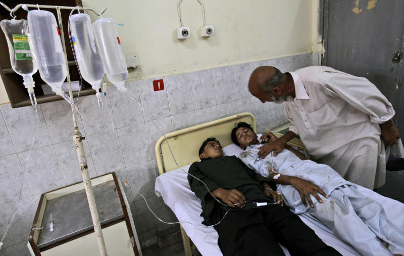 Pakistani youths, who were injured in a bus accident, are comforted by a relative, while laying in a bed in Benazir Bhutto hospital, in Rawalpindi, Pakistan, Monday, June 4, 2012. At least 25 members of a wedding party died early Monday when their bus fell into a deep ravine, in the Pakistani town of Kahuta near Rawalpindi, police said. (AP Photo/Muhammed Muheisen)