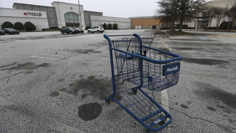 A few vehicles and an abandoned shopping cart are seen outside one of the entrances to Macy's at Stonecrest Mall in Stonecrest, Ga. (Curtis Compton/Atlanta Journal-Constitution via AP)