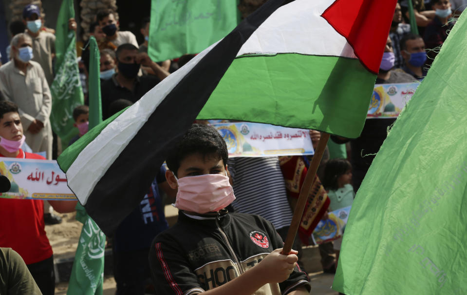 Hamas supporters wear face masks while waving the national flags during a protest against French President Emmanuel Macron and the publishing of caricatures of the Muslim Prophet Muhammad they deem blasphemous, at the main road of Jebaliya refugee camp, Gaza Strip, Friday, Oct. 30, 2020. (AP Photo/Adel Hana)