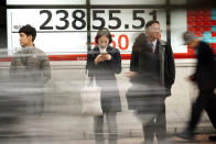 People stand in front of an electronic stock board showing Japan's Nikkei 225 index at a securities firm in Tokyo Friday, Jan. 24, 2020. Shares are mostly higher in quiet trading as China closes down for its week-long Lunar New Year festival. (AP Photo/Eugene Hoshiko)