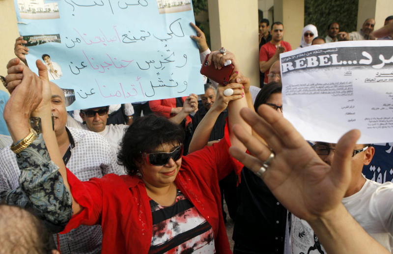 """Enas Abdel-Dayem, head of the Cairo Opera House, center, is greeted by Egyptian employees and activists as they chant anti-Muslim Brotherhood slogans during a protest demanding the resignation of the Egyptian culture minister at the opera house garden in Cairo, Egypt, Thursday, May 30, 2013. The Cairo Opera House has become a new battleground between supporters and opponents of Egypt's Islamist president, this time fighting over the direction of the Middle East s oldest music institution. The new culture minister fired the opera s head in what he calls a campaign to bring in new blood across the artistic scene. But her staff refuse any new boss and have closed the curtain on all performances, accusing the minister of bending to Islamist pressure. Arabic reads, """"who are you to prevent our fingers from playing, our throats from singing and our legs to dance."""" (AP Photo/Amr Nabil)"""