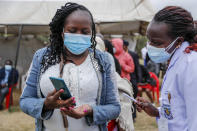 A woman uses her mobile phone to show to nurses the confirmation text message received that proves she has registered to receive the AstraZeneca coronavirus vaccine, at Kenyatta National Hospital in Nairobi, Kenya Thursday, Aug. 26, 2021. Wealthier nations are awash in vaccines, while they are scarce in poorer countries and many people are still waiting for their first shot. (AP Photo/Brian Inganga)