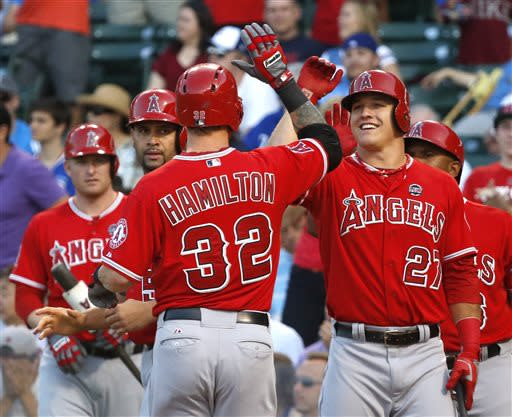 Los Angeles Angels' Josh Hamilton (32) is greeted at home by Mike Trout (27) and Albert Pujols, center left, after hitting a three-run home run off Chicago Cubs starting pitcher Jeff Samardzija during the first inning of an interleague baseball game Wednesday, July 10, 2013, in Chicago. (AP Photo/Charles Rex Arbogast)