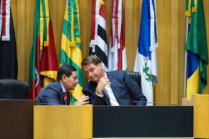 BRASILIA, BRAZIL - FEBRUARY 19: (L-R) Vice President of Brazil Hamilton Mourão talks with President of Brazil Jair Bolsonaro duringthe inauguration ceremony of the new president of the Superior Labor Tribunal (TST) Minister Cristina Peduzzion February 19, 2020 in Brasília, Brazil.After 72 years a Woman is Appointed to Take Office at the TST.(Photo by Andressa Anholete/Getty Images)