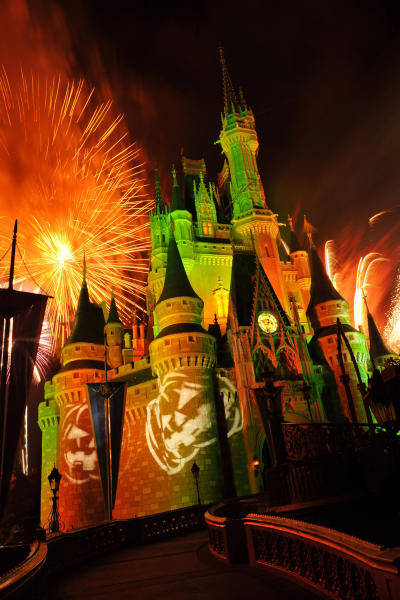 """This undated image released by Disney shows orange fireworks exploding over Cinderella's Castle while illuminated pumpkins are projected with light during the """"Happy HalloWishes"""" fireworks show at Magic Kingdom in Lake Buena Vista, Fla. (AP Photo/Disney, Gene Duncan)"""