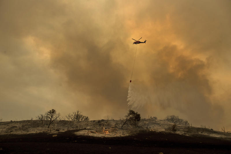 FILE - In this Dec. 9, 2017 file photo, a helicopter drops water while trying to keep a wildfire from jumping Santa Ana Road near Ventura, Calif. An investigation has determined that one of the largest and most destructive fires in California history was sparked by power lines coming into contact during high winds. The Ventura County Fire Department says Wednesday that the contact ignited dry brush on December 4, 2017 and eventually blackened more than 440 square miles (1,139 square kilometers). The Thomas fire destroyed more than a thousand structures in Ventura and Santa Barbara counties and resulted in the deaths of two people. (AP Photo/Noah Berger, File)