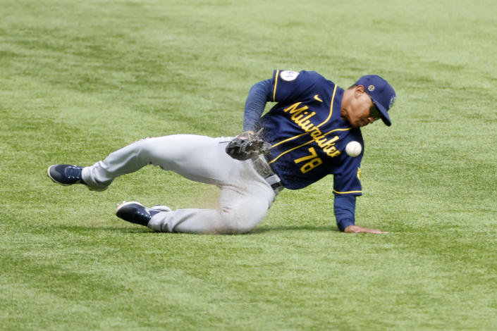 Milwaukee Brewers center fielder Corey Ray (78) traps a ball on a single hit by Texas Rangers first baseman Nate Lowe (30) during the fifth inning of a preseason baseball game Tuesday, March 30, 2021, in Arlington, Texas. (AP Photo/Michael Ainsworth)