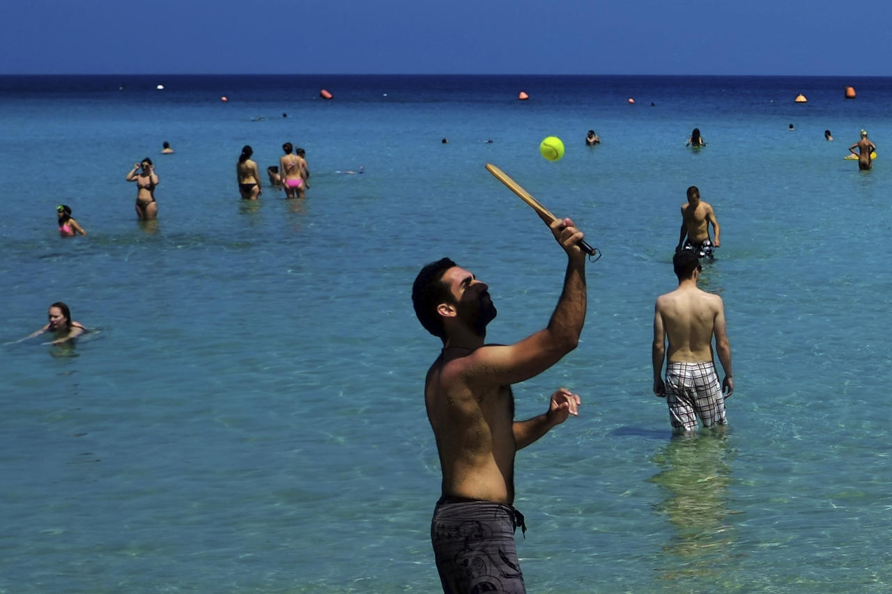 "FILE - In this Sunday, May 25, 2014 file photo, a man plays with a ball as other tourists enjoy the sea at ""Konnos"" beach near Ayia Napa, Cyprus. The mayor of Ayia Napa Yiannis Karousos, the seaside town that has long been a favorite for hundreds of thousands of holidaymakers annually, wants to keep out boorish, ill-mannered louts that he says on Wednesday, March 14, 2018, give his town a bad name and infuriate locals and other tourists alike. (AP Photo/Petros Karadjias, File)"