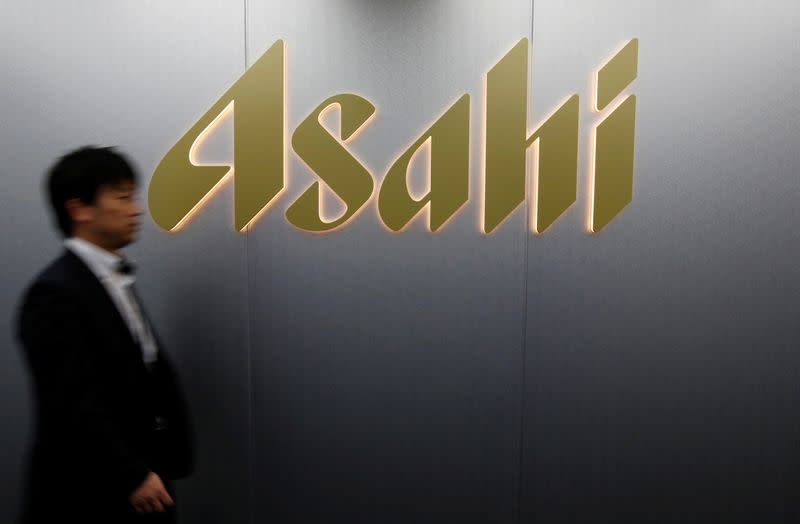 Man walks past the logo of Asahi Group Holdings at the company's headquarters in Tokyo