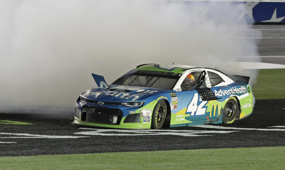 Kyle Larson holds the steering wheel out of the car as he performs a burnout after winning the NASCAR All-Star Race at Charlotte Motor Speedway in Concord, N.C., Saturday, May 18, 2019. (AP Photo/Chuck Burton)