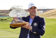 Brooks Koepka poses with the trophy after winning a PGA golf tournament on Sunday, Feb. 7, 2021, in Scottsdale, Ariz. (AP Photo/Rick Scuteri)
