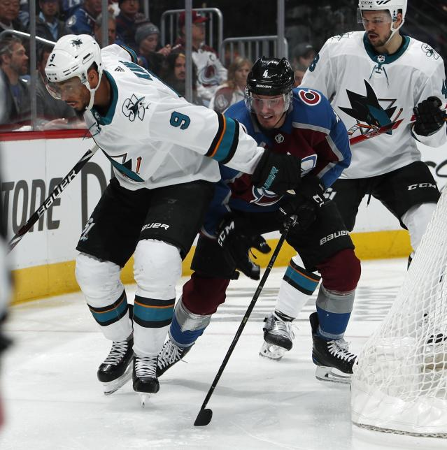 San Jose Sharks left wing Evander Kane, left, fights to wrap around the net for a shot as Colorado Avalanche's Tyson Barrie defends during the second period of Game 4 of an NHL hockey second-round playoff series Thursday, May 2, 2019, in Denver. (AP Photo/David Zalubowski)