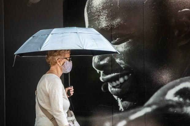 A woman walks with an umbrella to provide shade in Vancouver on June 30.  (Ben Nelms/CBC - image credit)