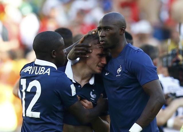 France's Antoine Griezmann is consoled by teammates Rio Mavuba and Eliaquim Mangala after losing against Germany during their 2014 World Cup quarter-finals at the Maracana stadium in Rio de Janeiro July 4, 2014. REUTERS/Darren Staples (BRAZIL - Tags: SOCCER SPORT WORLD CUP)