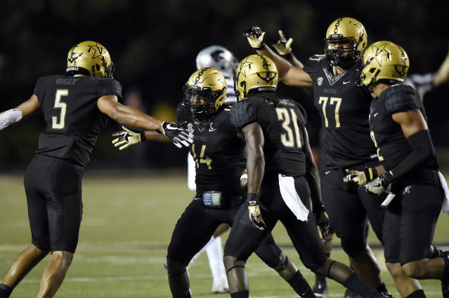 "Vanderbilt safety <a class=""link rapid-noclick-resp"" href=""/nhl/players/4323/"" data-ylk=""slk:Ryan White"">Ryan White</a> (14) celebrates <a class=""link rapid-noclick-resp"" href=""/ncaaf/players/243057/"" data-ylk=""slk:LaDarius Wiley"">LaDarius Wiley</a> (5), <a class=""link rapid-noclick-resp"" href=""/ncaaf/players/243042/"" data-ylk=""slk:Tre Herndon"">Tre Herndon</a> (31) and <a class=""link rapid-noclick-resp"" href=""/ncaaf/players/243043/"" data-ylk=""slk:Nifae Lealao"">Nifae Lealao</a> (77) after White intercepted a pass against Kansas State. (AP Photo/Mark Zaleski)"