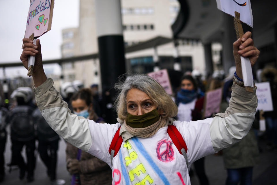 A protester holds up placards during an unauthorised demonstration against COVID-19 restrictive measures in Brussels, Sunday, Jan. 31, 2021. According to Belgian media around 200 people have been arrested for trying to join a protest against restrictive measures implemented in the country in order to fight the virus, such as a 10pm curfew or the closing of bars and restaurants. (AP Photo/Francisco Seco)