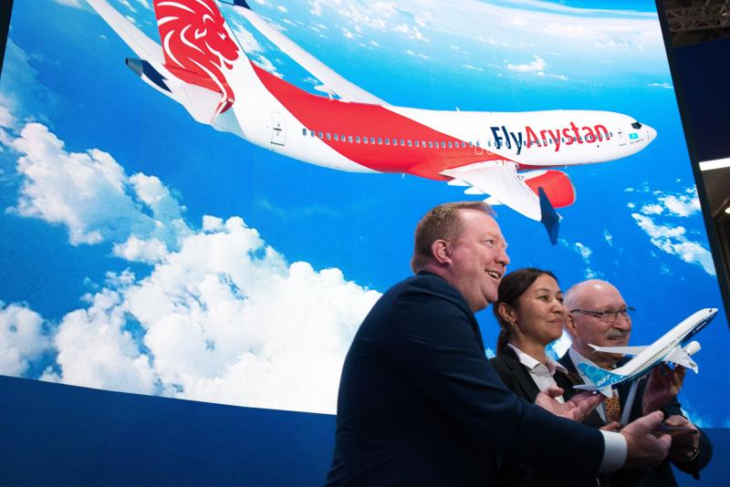 From left; Boeing Commercial Airplanes president and CEO Stanley A. Deal, Air Astana chief planning officer Alma Aliguzhinova and Air Astana chief operating officer Anthony Regan pose after a news conference at the Dubai Airshow in Dubai, United Arab Emirates, Tuesday, Nov. 19, 2019. Kazakhstan's national carrier Air Astana announced Tuesday a letter of intent to purchase 30 of Boeing's 737-8 Max jets for its new budget airliner FlyArystan. (AP Photo/Jon Gambrell)