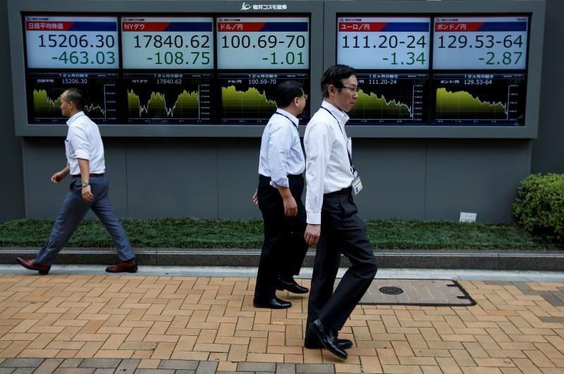 Passersby walk past in front of electronic boards showing Japan's Nikkei share average, the Japanese yen's exchange rate against the U.S. dollar, British pound and Euro outside a brokerage in Tokyo, Japan