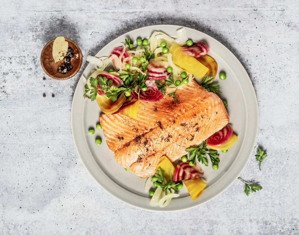 Pan fried salmon with vegetables on gray background