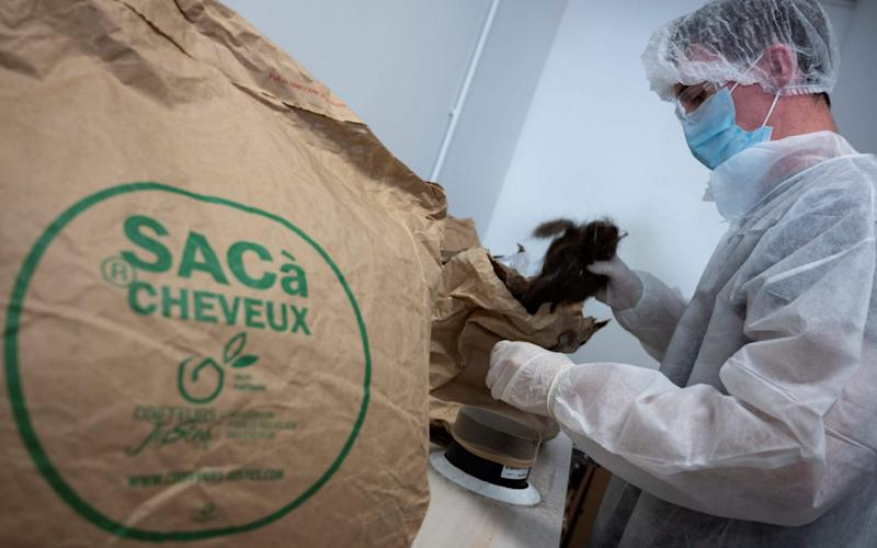 A worker fills paper bags with hairs received from hairdressers in France and used to make hydrocarburant absorbent draft snake - CHRISTOPHE SIMON/AFP