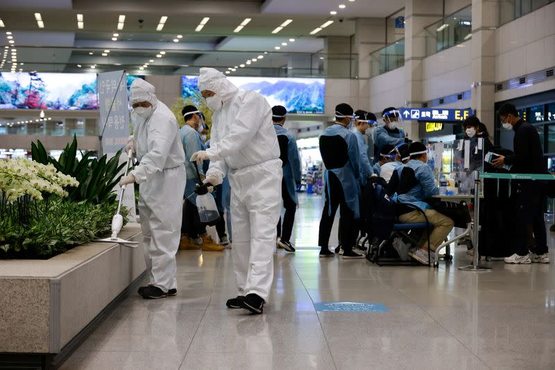 Workers wearing protective gear disinfect an arrival gate as other workers check passengers from overseas upon their arrival at the Incheon International Airport, in Incheon