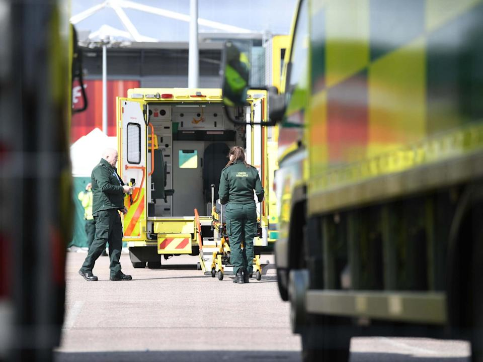 Paramedics preparing an ambulance at the ExCel centre in London which is being made into a temporary NHS Nightingale hospital during the coronavirus outbreak: PA