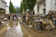Residents clear mud and unusable furniture from houses in the city center of Bad Neuenahr, western Germany, Saturday, July 17, 2021. Heavy rains caused mudslides and flooding in the western part of Germany. Multiple have died and are missing as severe flooding in Germany and Belgium turned streams and streets into raging, debris-filled torrents that swept away cars and toppled houses. (Thomas Frey/dpa via AP)