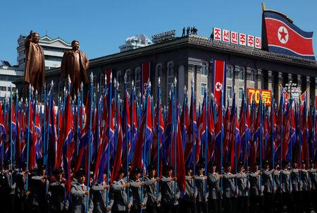 People carry flags in front of statues of North Korea founder Kim Il Sung (L) and late leader Kim Jong Il during a military parade marking the 70th anniversary of North Korea's foundation in Pyongyang