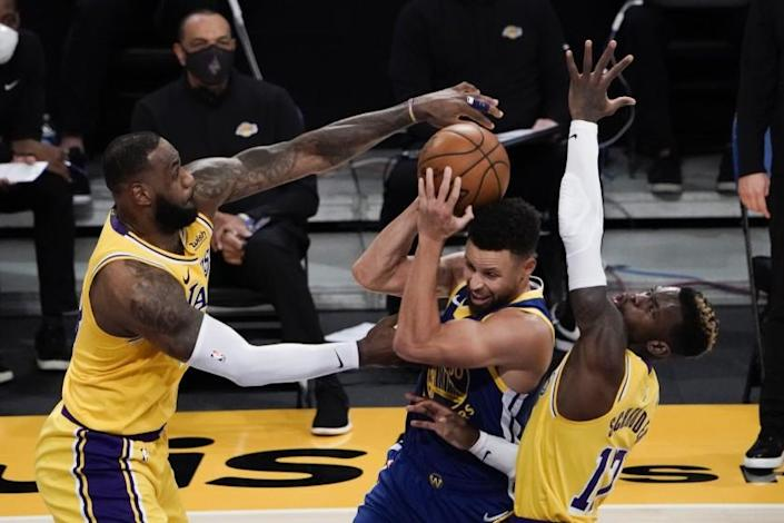 Los Angeles Lakers' LeBron James, left, and Dennis Schroder, right, defend against Golden State Warriors.