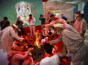 Hindus offer prayers for a groundbreaking ceremony of a temple dedicated to the Hindu god Ram in Ayodhya, at the Vishwa Hindu Parishad, or World Hindu Council, headquarters in New Delhi, India, Wednesday, Aug. 5, 2020. The coronavirus is restricting a large crowd, but Hindus were joyful before Prime Minister Narendra Modi breaks ground Wednesday on a long-awaited temple of their most revered god Ram at the site of a demolished 16th century mosque in northern India. (AP Photo/Manish Swarup)