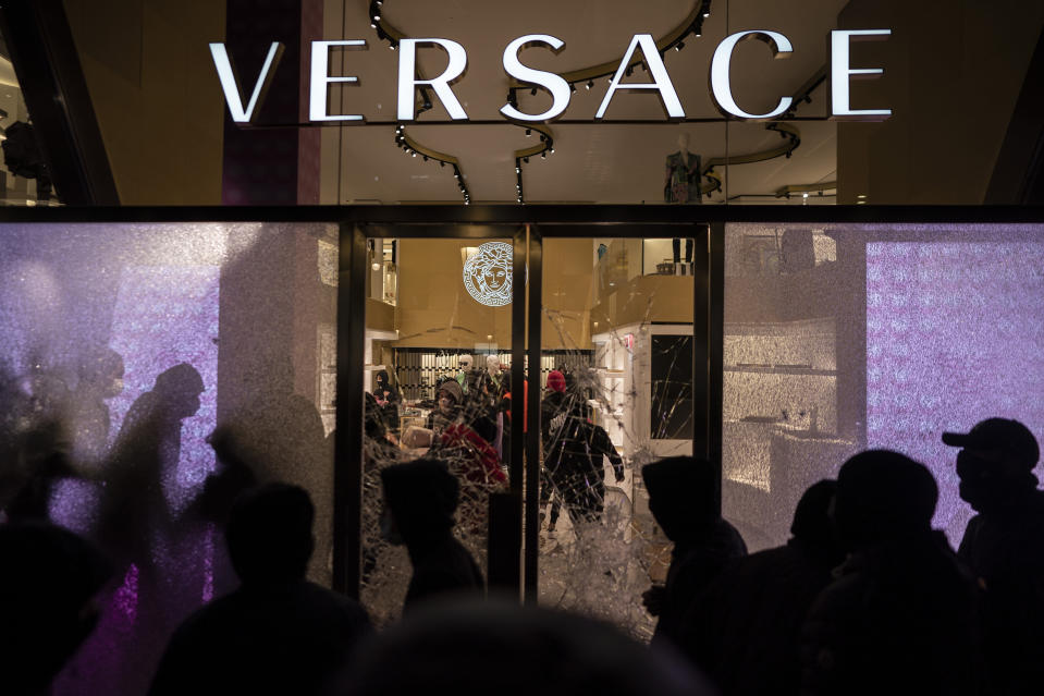 People loot a Versace store during a protest condemning the arrest of rap singer Pablo Hasél in Barcelona, Spain, Saturday, Feb. 20, 2021. A fifth night of peaceful protests to denounce the imprisonment of a Spanish rap artist once more devolved into clashes between police and fringe group members who set up street barricades and smashed storefront windows in Barcelona. (AP Photo/Felipe Dana)