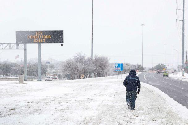 PHOTO: A pedestrians walks past a road sign warning commuters of icy conditions on a road in Austin, Texas, Feb. 18, 2021.  (Thomas Ryan Allison/Bloomberg via Getty Images)