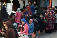 People queue outside a charity kitchen to get food donations in Sanaa, Yemen