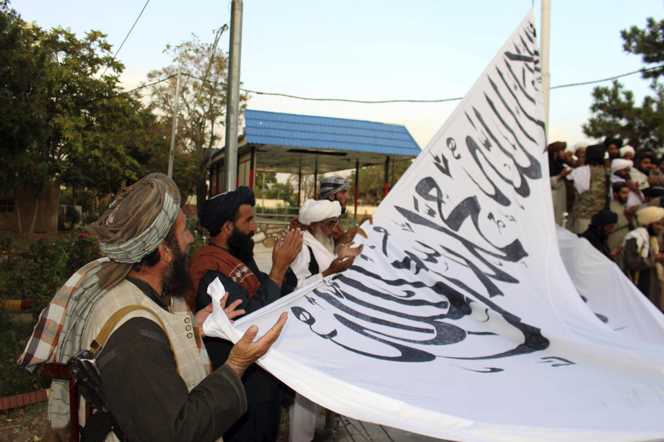 FILE - In this Aug. 15, 2021 file photo, Taliban fighters pray while raising their flag at the Ghazni provincial governor's house, in Ghazni, southeastern, Afghanistan. Twin tragedies on opposite sides of the world are piling misery on people that have seen far more than their share. In Afghanistan, a group of gunmen known for sadistic tyranny rocketed back into power after 20 years as Western and Afghan leaders walked away with a sad shrug. (AP Photo/Gulabuddin Amiri, File)
