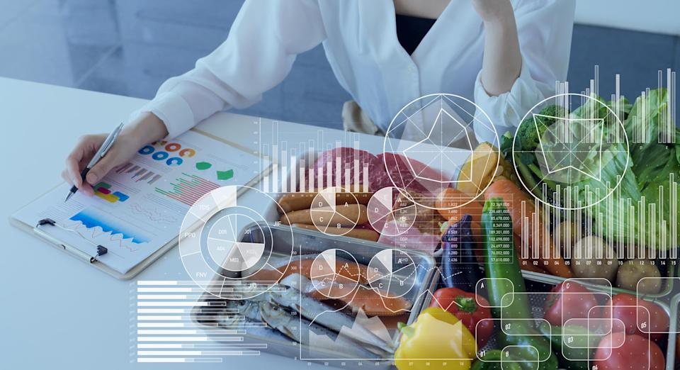 A researcher in a lab coat sits next to an array of foods overlaid with graphs and charts.