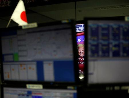 FILE PHOTO - U.S. Republican presidential nominee Donald Trump is seen between monitors on TV news at a foreign exchange trading company in Tokyo