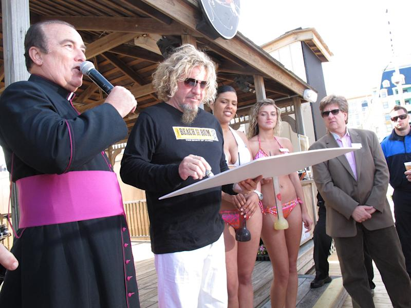 Monsignor William Hodge of St. Nicholas Roman Catholic Church in Atlantic City N.J., left, thanks rocker Sammy Hagar for a $10,000 donation to his church's food pantry on May 18, 2012. The former Van Halen singer told The Associated Press he's not surprised the Van Halen tour appears to be crumbling, with dozens of dates postponed. (AP Photo/Wayne Parry)