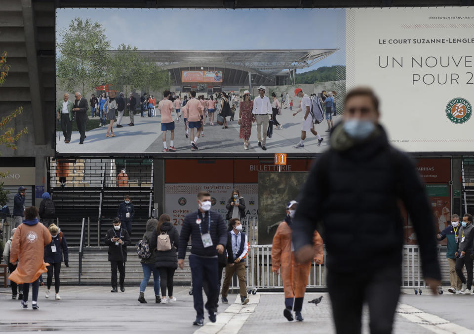 The image on a billboard of spectators with straw hats walking the sunny lanes of the Roland Garros grounds contrasts with the changed reality as spectators with face mask walk under damp and cold conditions during first round matches of the French Open tennis tournament at the Roland Garros stadium in Paris, France, Sunday, Sept. 27, 2020. (AP Photo/Alessandra Tarantino)