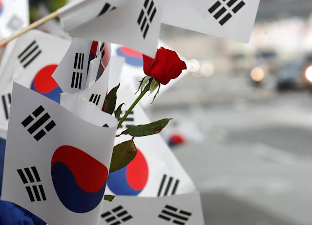 <p>South Korean flags and a flower is seen waved by people as a convoy transporting South Korean President Moon Jae-in leaves the Presidential Blue House for the inter-Korean summit in Seoul, South Korea, April 27, 2018. (Photo: Jorge Silva/Reuters) </p>