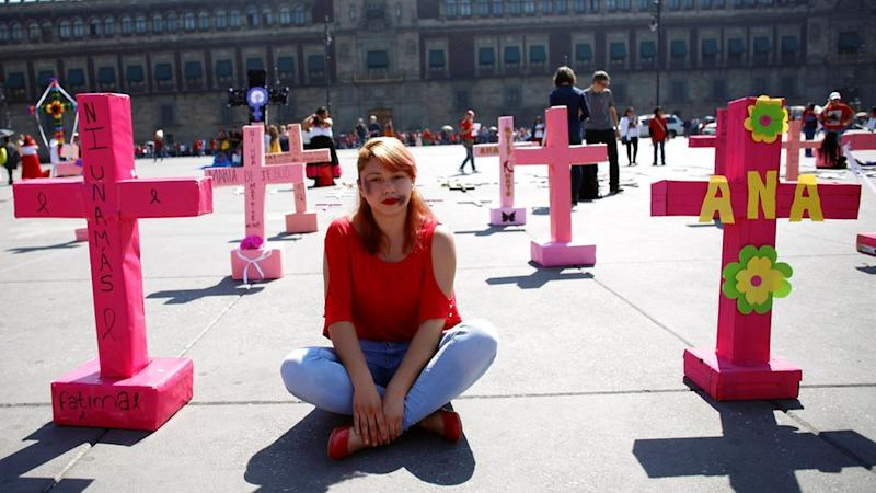 """A woman sits among pink crosses during the """"Day without women"""" protest in Mexico"""