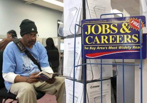 A job seeker waits to use a phone at a career center in Richmond, Calif. Economist Jack Kyser predicts that the state's jobless rate will average 12.6% next year, but other economists call his prediction overly pessimistic.
