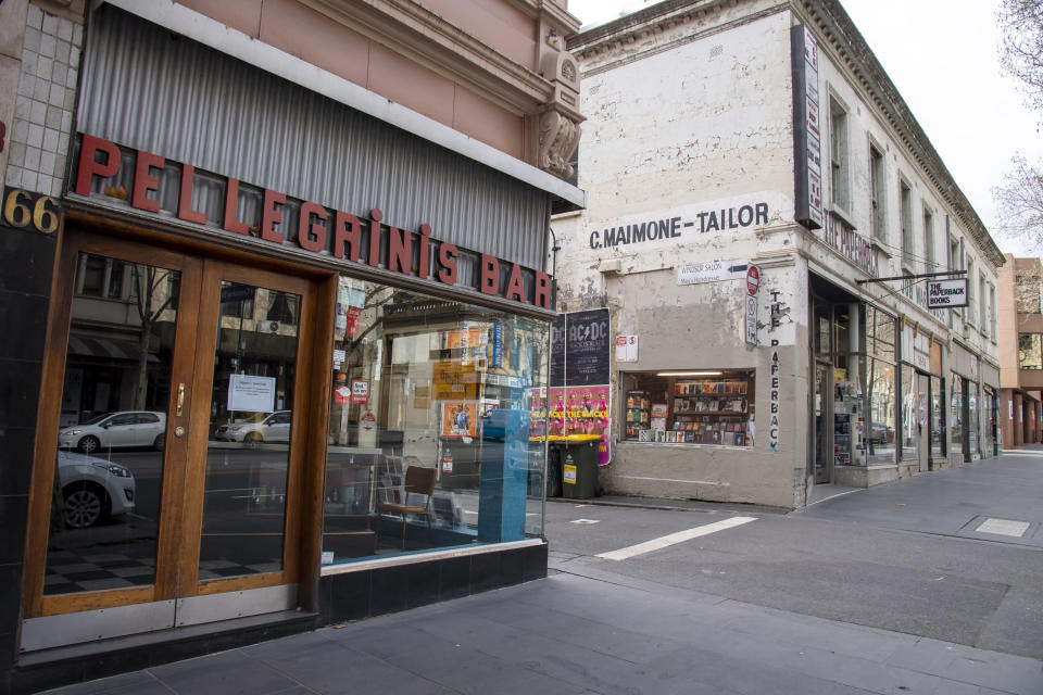 Pellegrinis Cafe and The Paperback book store are closed during lockdown due to the continuing spread of the coronavirus in Melbourne, Thursday, Aug. 6, 2020. Victoria state, Australia's coronavirus hot spot, announced on Monday that businesses will be closed and scaled down in a bid to curb the spread of the virus. (AP Photo/Andy Brownbill)
